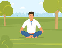 Man is doing yoga and sitting in the lotus position in the park Stock Photo