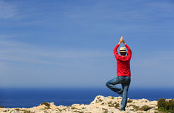 Man doing yoga in summer mountains Stock Photo