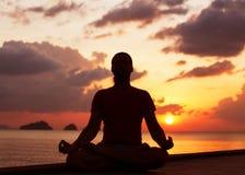 Man doing yoga at sunset Stock Images