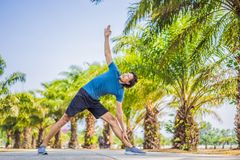 Man doing yoga in a tropical park royalty free stock image
