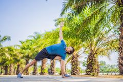 Man doing yoga in a tropical park stock images