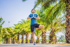 Man doing yoga in a tropical park royalty free stock photos