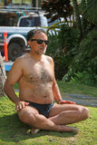 Man doing yoga. Man wearing sunglasses and bathing suit doing yoga outdoors on grassy area on sunny day Royalty Free Stock Images