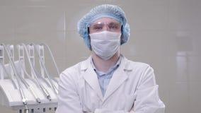 Man doktorskirurgen i en maskering och lockställningar i ett fungeringsrum i tand- klinik arkivfilmer