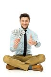 Man with dollar bills showing thumbs up Stock Image