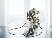 Man in dollar trap. Worshipping man inside abstract dollar sign trap in interior with city view and daylight. 3D Rendering Royalty Free Stock Photography