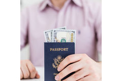 Man with dollars inside passport Stock Photos