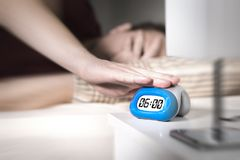 Man don`t want to wake up for work in the morning. Turning off alarm clock or press snooze button with hand. Lazy person unable to get out of bed. Bad monday Stock Images