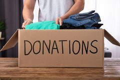 Man Donating Clothes In Donation Box. Young Man Donating Clothes In Donation Box Over Wooden Desk royalty free stock images