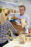 Man Donating Unwanted Items To Charity Shop. Man Donates Unwanted Items To Charity Shop Royalty Free Stock Image