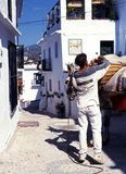 Man with donkey in village street, Frigiliana. Stock Photo