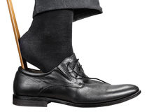 Man dons black shoe with shoehorn isolated Royalty Free Stock Images