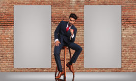 Man in double breasted suit sitting near two blank billboards Royalty Free Stock Photography