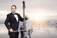 Man with doublebass standing by the ocean Royalty Free Stock Photography