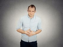 Man, doubling over in acute body stomach pain Royalty Free Stock Images