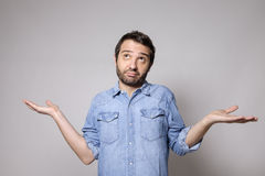 Man doubtful  on gray background Stock Images