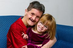 Man With Downs Syndrome Hugs His Great Niece Both Smiling. An older men with Downs Syndrome and no teeth holds his great niece in his lap and hugs her. Both are royalty free stock photography