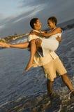 Man Dragende Vrouw in de Oceaan stock afbeeldingen