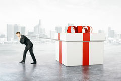 Man dragging present box. Businessman dragging huge present box on abstract city background. 3D Rendering vector illustration