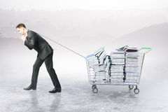 Man dragging trolley with books. Businessman dragging trolley with heap of books on abstract background. Education concept. 3D Rendering Stock Photography