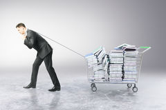 Man dragging trolley with books. Businessman dragging trolley with heap of books on grey background. Education concept. 3D Rendering Royalty Free Stock Image
