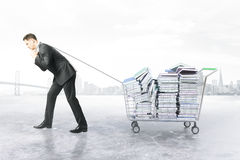 Man dragging trolley with books. Businessman dragging trolley with heap of books on white background. Education concept. 3D Rendering Royalty Free Stock Photos