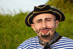 Man with drawed beard and whiskers in pirate suit. Portrait of smiling man with drawed beard and whiskers in pirate suit in early fall evening park Royalty Free Stock Images