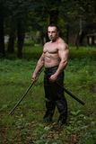 Man Drawing Ancient Sword In Self Defense. Action Hero Muscled Man Holding A Ancient Sword - Standing In Forest Wearing Leather Pants Stock Photography