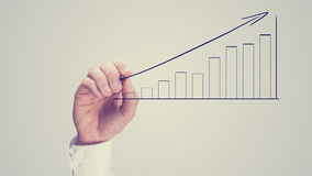 Man drawing an ascending bar graph Stock Images