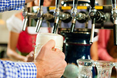 Man drawing beer from tap in Bavarian pub Royalty Free Stock Images