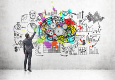 Man drawing  a brain sketch on concrete. Rear view of a businessman in a suit drawing a brain sketch with gears on a concrete wall. There is also a startup Stock Images