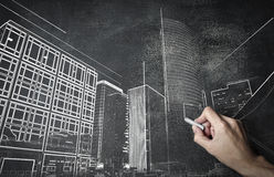 Man drawing buildings on a backboard Royalty Free Stock Photography