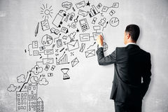 Man drawing business icons. Businessman drawing creative business icons on concrete wall. Success concept Stock Photo