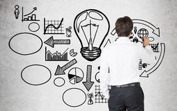 Man drawing business idea icons on concrete Royalty Free Stock Photo