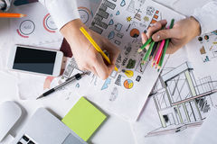 Man drawing business sketch. Top view of man`s hands drawing creative business sketch with colorful pencils on desktop with blank smartphone and other items royalty free stock images