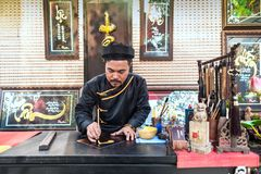 Man drawing calligraphy in Vietnam. HOCHIMINH CITY- VIETNAM: Old men with traditional black costume drawing calligraphy ancient distich in Hochiminh city royalty free stock image