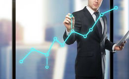 Man drawing chart. Businessman drawing chart on city background Stock Photography