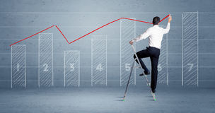 Man drawing chart from ladder Stock Photo