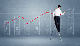 Man drawing chart from ladder Royalty Free Stock Photos