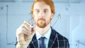 Man Drawing Dollar Sign on Growth Graph on Transparent Glass, Red Hairs. 4k , high quality Royalty Free Stock Photo