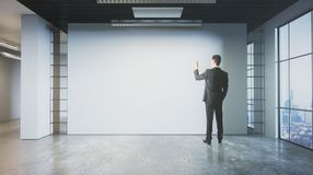 Man drawing on empty wall. Back view of young businessman drawing on empty wall of grunge interior with city view. Mock up, 3D Rendering Stock Image