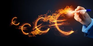 Man drawing euro symbol. Burning euro sign drawn by businessman on dark background Royalty Free Stock Photography