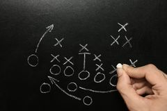 Man drawing football game scheme on chalkboard. Top view royalty free stock photography