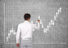 Man drawing forex chart. Businessman drawing forex chart on wall Stock Photography