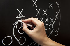 Man drawing a game strategy. With white chalk on a blackboard Royalty Free Stock Image