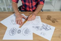 Man drawing gear wheel on paper using pencil and ruler royalty free stock photo