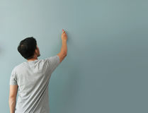 Man drawing gesture with white chalk on chalkboard or wall. Royalty Free Stock Photography