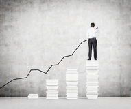 Man drawing graph of stock. Businessman drawing graph of stock on concrete wall Royalty Free Stock Image
