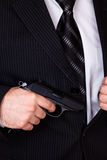 Man drawing his gun from jacket pocket Royalty Free Stock Image