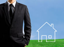 Man drawing a house in a field Stock Image
